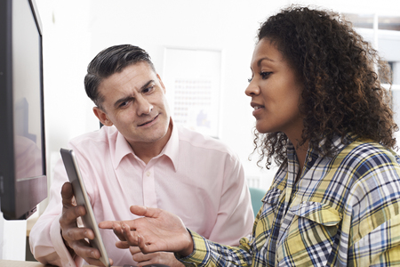 Man Training Woman In Office Using Digital Tablet Banque d'images