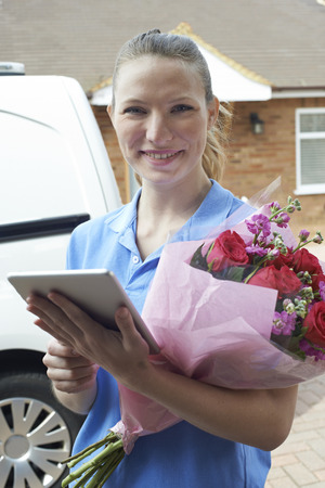 Portrait Of Florist With Digital Tablet Making Home Delivery Of Bouquet