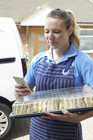 Female Caterer Delivering Tray Of Sandwiches To House Checking Text Message On Mobile Phone