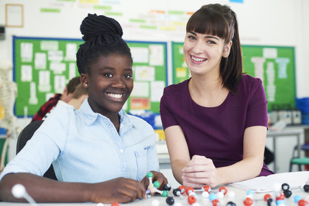 Portrait Of Female Pupil And Teacher Using Molecular Model Kit In Science Lesson