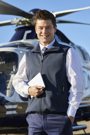 Portrait Of Smiling Pilot Standing In Front Of Helicopter With Digital Tablet