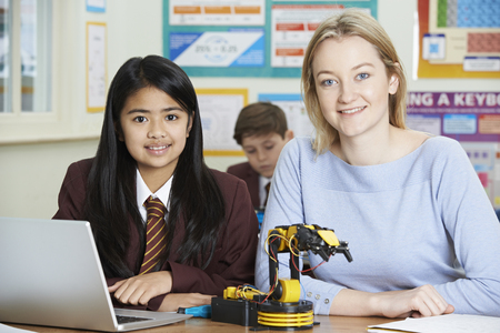 Portrait Of Teacher With Female Pupil In Science Lesson Studying Robotics