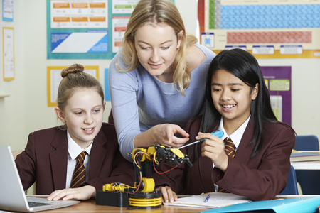 Teacher With Female Pupils In Science Lesson Studying Robotics