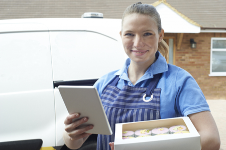 Portrait Of Female Baker With Digital Tablet Making Home Delivery Of Cupcakes Stock Photo