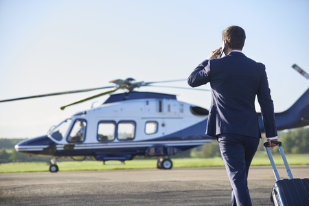 Rear View Of Businessman Walking Towards Helicopter Whilst Talking On Mobile Phone
