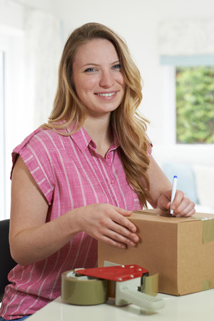Portrait Of Woman At Home Writing Address On Package