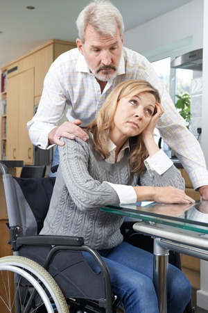 Man Comforting Depressed Woman In Wheelchair At Home Imagens