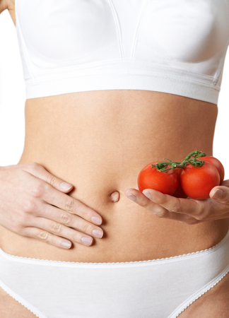 Close Up Of Woman In Underwear Holding Tomatoes And Touching Stomach