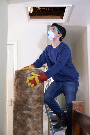 Man Climbing Into Loft To Insulate House Roof  Stock fotó