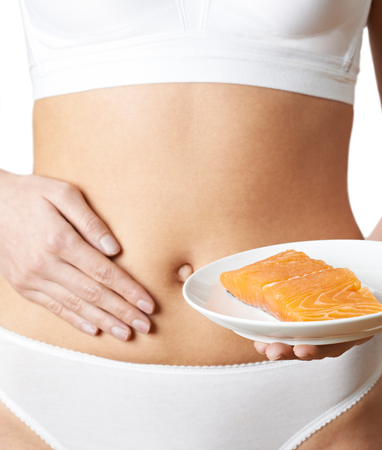 Close Up Of Woman In Underwear Plate Of Salmon And Touching Stomach