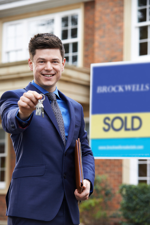 Male Realtor Standing Outside Residential Property Holding Keys