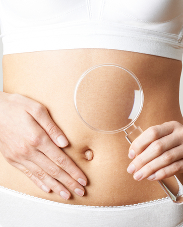 Close Up Of Woman Wearing Underwear Holding Magnifying Glass And Touching Stomach