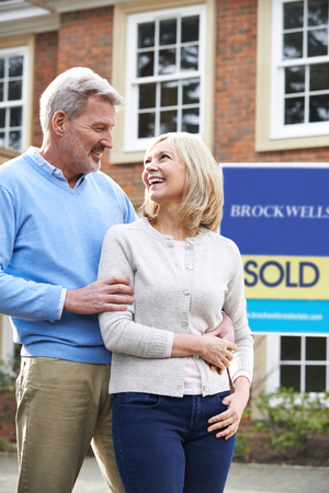 Mature Couple Standing Outside New Home With Sold Sign Stock fotó