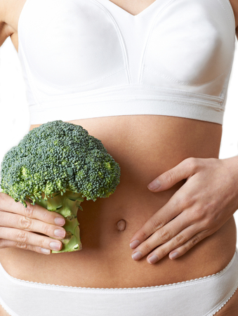 Close Up Of Woman In Underwear Holding Bunch Of Broccoli And Touching Stomach