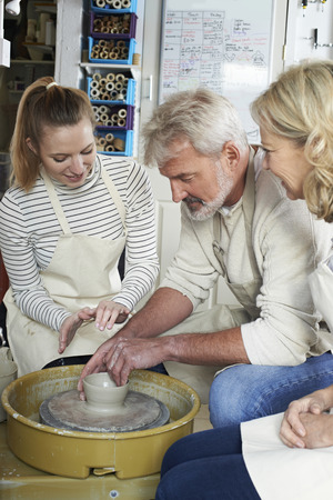 Mature Couple With Teacher In Pottery Class Stock fotó