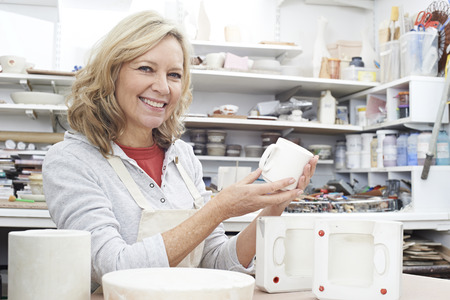 Portrait Of Mature Woman In Pottery Studio Casting Mug Stock fotó