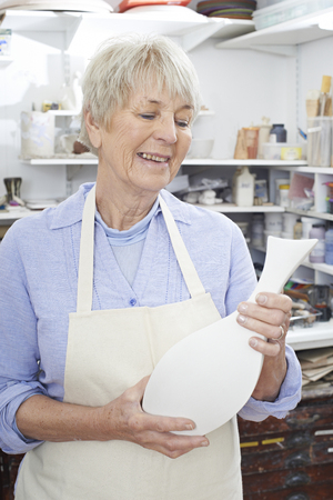 Senior Woman Holding Vase In Pottery Studio