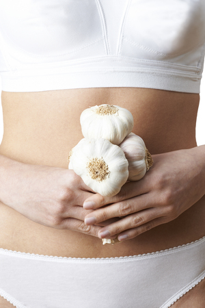 Close Up Of Woman In Underwear Holding Bunch Of Garlic