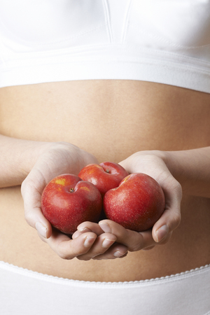 Close Up Of Woman In Underwear Holding Fresh Plums Stock fotó