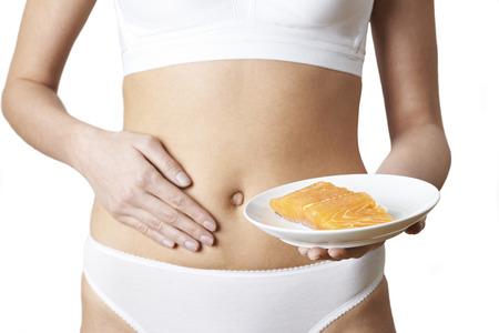 Woman In Underwear holding a plate of Salmon And Touching Stomach