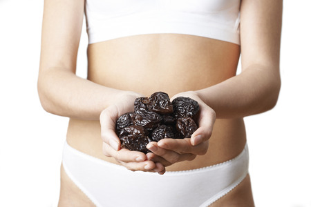 Close Up Of Woman In Underwear Holding Dried Prunes