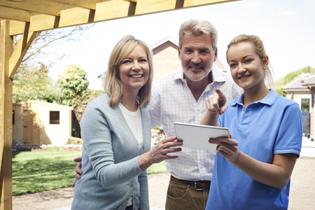Mature Couple Discussing Plan On Digital Tablet With Landscape Gardener