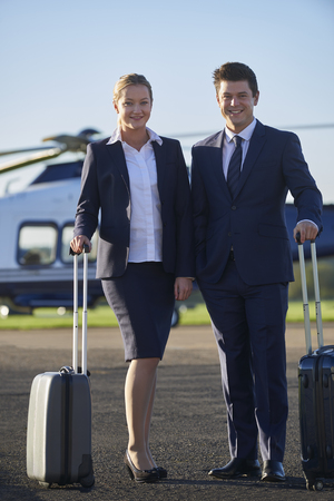 Portrait Of Businessman And Businesswoman Standing In Front Of Helicopter  Stock fotó