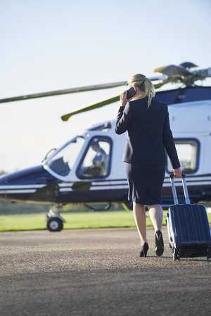 Rear View Of Businesswoman Walking Towards Helicopter Whilst Talking On Mobile Phone