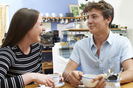 Teenage Couple Meeting In Cafe And Drinking Cup Of Coffee