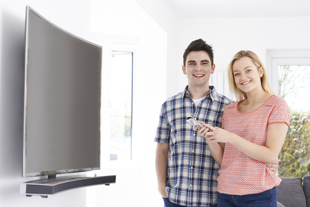 Portrait Of Young Couple With New Curved Screen Television At Home Stock fotó