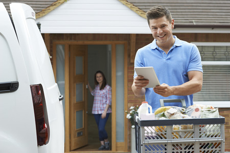 Portrait Of Driver Delivering Online Grocery Order To House Using Digital Tablet