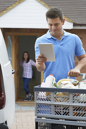 Driver Delivering Online Grocery Order To House Using Digital Tablet