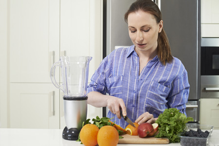 Woman In Kitchen Chopping Fruit To Put Into Juicer Stock fotó