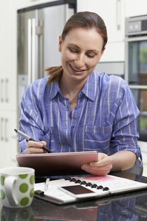 Female Freelance Worker Using Digital Graphics Tablet At Home Stock fotó