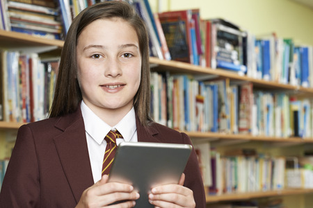 Portrait Of Girl Wearing School Uniform Using Digital Tablet In Library Stock fotó