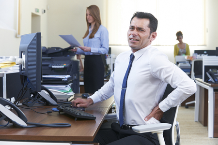 Businessman Working At Desk Suffering From Backache Stock fotó