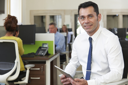 Portrait Of Businessman With Digital Tablet Sitting In Busy Modern Office