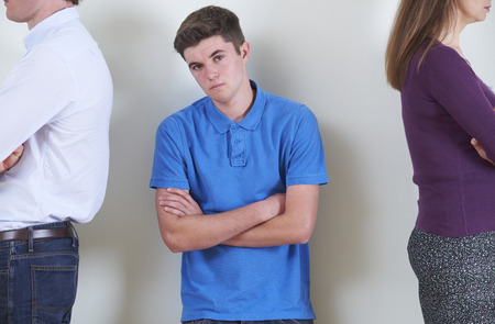 Portrait Of Teenage Boy Standing Between Parents Who Are Ignoring Each Other