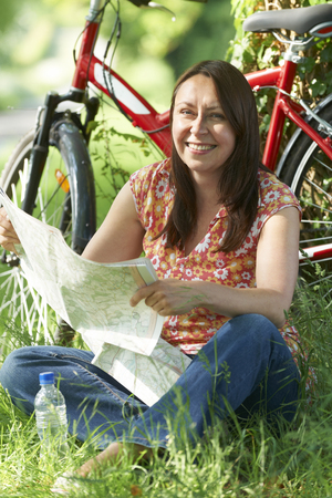 Portrait Of Mature Woman On Cycle Ride In Countryside Reading Map Stock fotó