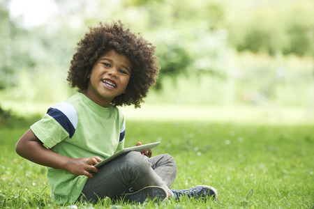 Young Boy Using Digital Tablet In Park