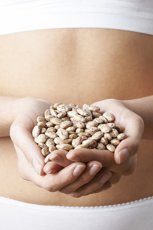 Close Up Of Woman In Underwear Holding Handful Of Pinto Beans