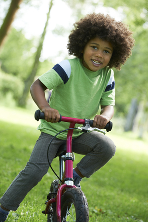 Young Boy Learning To Ride Bike In Park Stock fotó