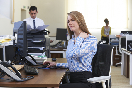 Businesswoman Working At Desk Suffering From Neck Pain