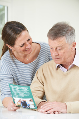 Senior Man With Adult Daughter Looking At Brochure For Retirement Home