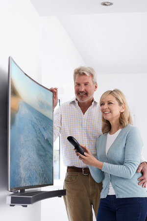 Mature Couple With New Curved Screen Television At Home Stock fotó