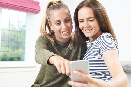 Teenage Girls Reading Text Message On Mobile Phone Stock fotó