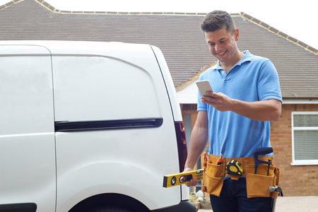 Builder With Van Checking Text Messages On Mobile Phone Outside House Stock fotó
