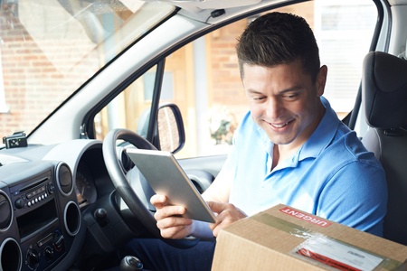 Courier In Van With Digital Tablet Delivering Package To House