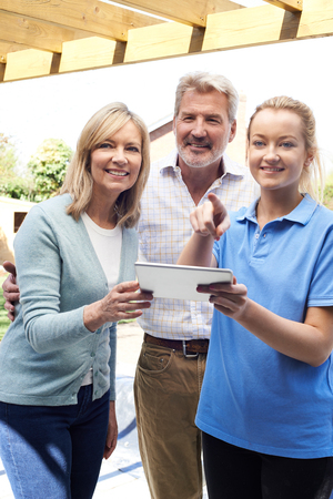 Mature Couple Discussing Plan With Landscape Gardener Using Digital Tablet