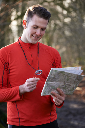 Man Orienteering In Woodlands With Map And Compass